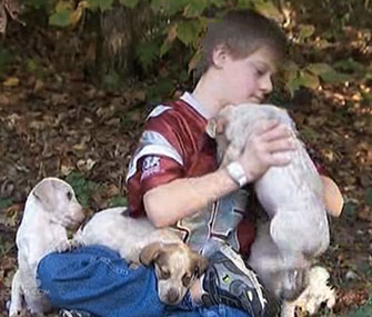 Kyle Camp plays with the puppies who kept him warm while he was lost in the woods.