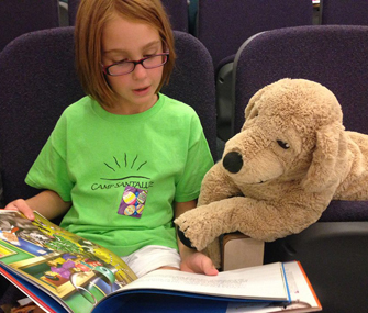 little girl reading a book with a stuffed animal dog