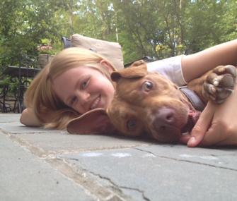 Girl hugging pitbull.