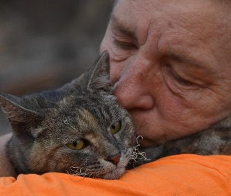 Debi Brusatori holds Ruthie Rosemary after finding her in the ruins of her burned out home.
