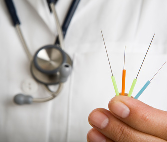 Doctor holding acupuncture needles