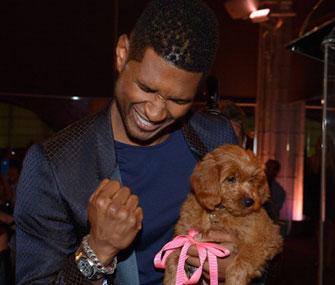 Usher celebrates winning his $12,000 Goldendoodle.