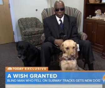 Cecil Williams sits with his retiring guide dog, Orlando, left, and his new dog, Godiva, right.