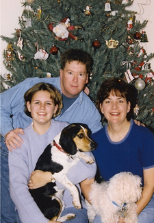 family in front of Christmas tree with Beagle and Maltese