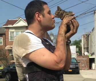 NYPD Officer John Passarella shares a sweet moment with the kitten he saved from a minivan's engine block.