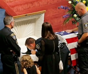 Oklahoma City police officer Sgt. Ryan Stark, center, leans over the casket of his canine partner, Kye