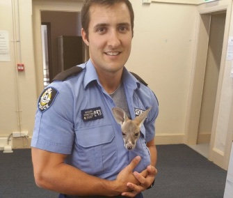 Cuejo cuddles with his hero, Cue, Australia, Police Constable Scott Mason.
