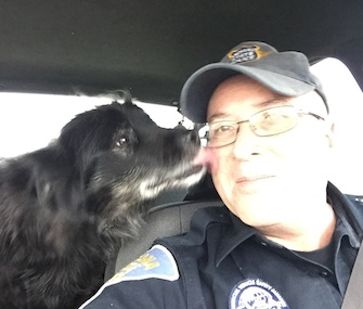 Sadie gives Indiana State Trooper Joe Swisher, a kiss after he rescued her from a busy roadway.
