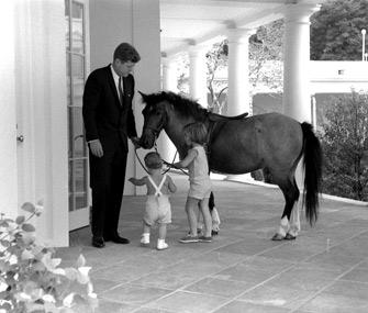 President John F. Kennedy with Caroline Kennedy's pony Macaroni