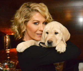 "Jenna Elfman of the NBC series ""Growing up Fisher"" holds a puppy who will trained to be a guide dog"