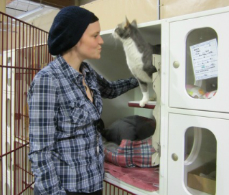 Humane society volunteer with cat on cat condo