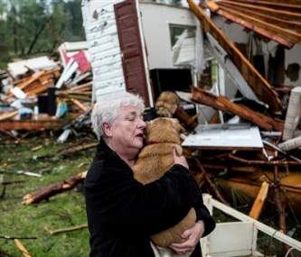 Constance Lambert embraces her dog after finding it in the rubble of her home in Tupelo, Mississippi.