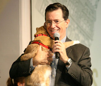 Comedian Stephen Colbert gets a hug from a cat at a book signing event.