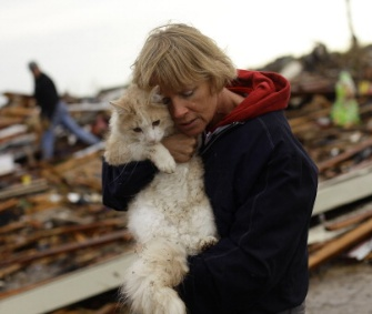 June Simson holds her cat, Sammi, who she found standing on the rubble of her home.